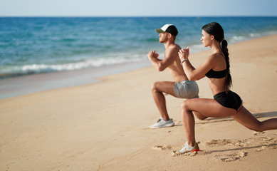 Healthy lifestyle. Young beautiful couple doing sports exercises at the beach.