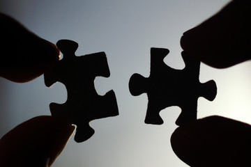 silhouette of two puzzle pieces in hands on sky background close-up. problem solving concept Wall mural