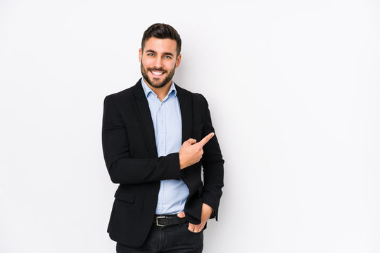 Young caucasian business man against a white background isolated smiling and pointing aside, showing something at blank space.