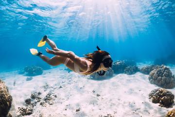 Fototapeta Freediver girl with fins glides over sandy bottom in blue ocean obraz