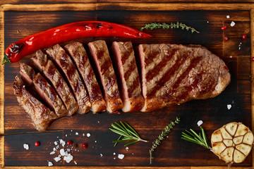 Keto ketogenic diet medium beef steak, grilled striploin on cutting board. Paleo food recipe with...
