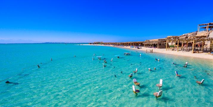 Orange Bay Beach with crystal clear azure water and white beach - paradise coastline of Giftun island, Mahmya, Hurghada, Red Sea, Egypt.