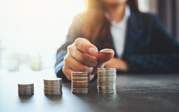 Businesswoman holding and stacking coins on the table