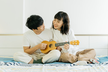 Young asian couple playing ukulele and sing a song together in bedroom with happy and relax.