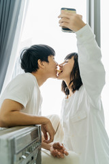 Young asian couple take a photo themself by smartphone with romance. Romantic and sweet scene of people falling in love.