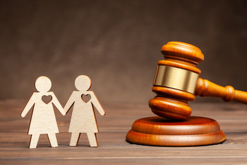 Illegal gay marriage. Two lesbians on the background of the judge's hammer. Law and marriage of same-sex people.