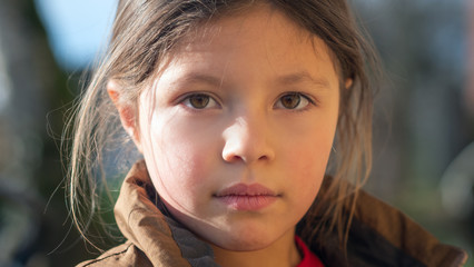 Authentic close up shot of cute little girl is smiling in camera outside her house on a sunny...
