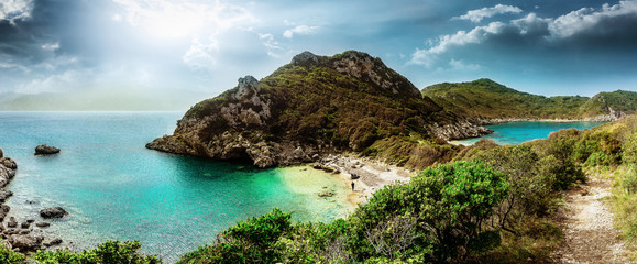 Wonderful summertime panoramic seascape. View of the cliff into the crystal clear azure sea bay and distant islands. Unique secluded beach. Agios Stefanos cape. Afionas. Corfu. Greece.