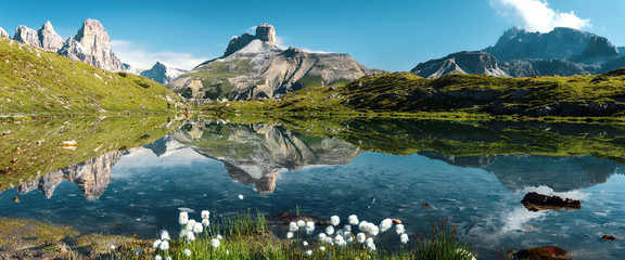 Zelfklevend Fotobehang Groen blauw Awesome Alpine highlands in sunny day. Amazing Summer Landscape of Dolomites Alps. Wonderful Panoramic view at Mountains Range and calm lake on foreground of Tre Cime di Lavaredo National park