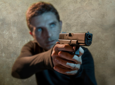 grunge cinematic portrait of attractive and dangerous looking hitman or secret service especial agent man in action pointing gun in crime mob and criminal lifestyle concept