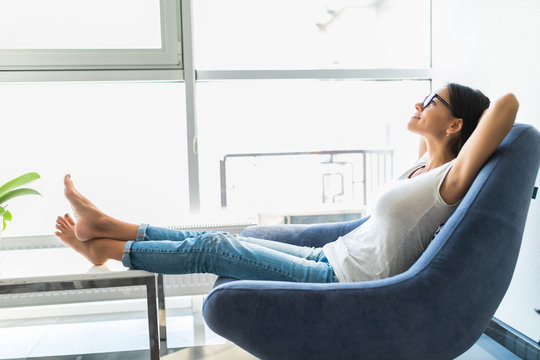 Young woman at home sitting on modern chair in front of window relaxing in her room