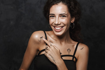 Image of beautiful happy woman smiling and pointing finger at her tattoo