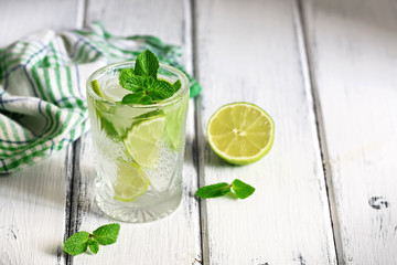 Refreshing cold drink with lime and mint in a glass on a white wooden board table. Traditional summer mojito cocktail. Selective focus, copy space Wall mural