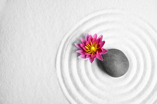 Zen garden. Beautiful lotus flower, stone and space for text on white sand, flat lay