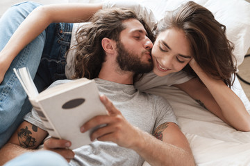 Loving couple indoors at home lies reading book together.