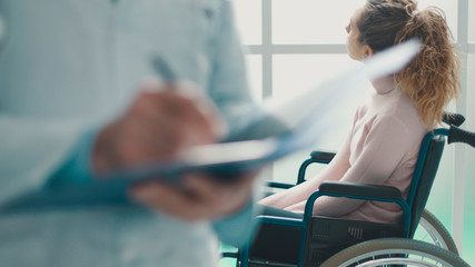 Doctor writing medical records and patient in a wheelchair