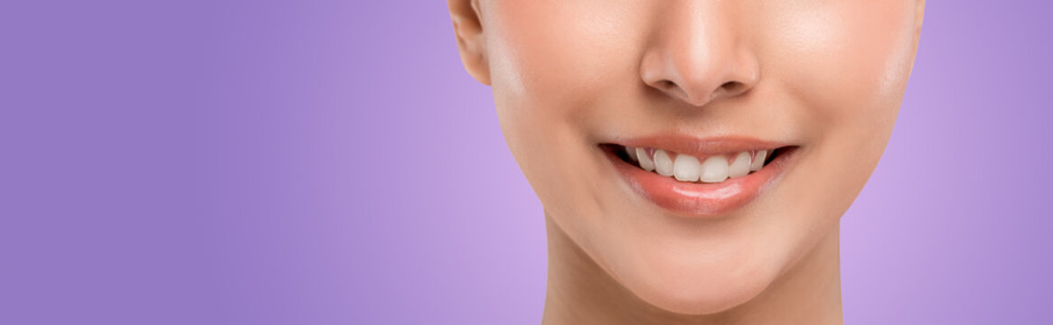 Close up part of the face. The perfect align teeth of young Caucasian teenager woman with smiley face. Isolated on purple.