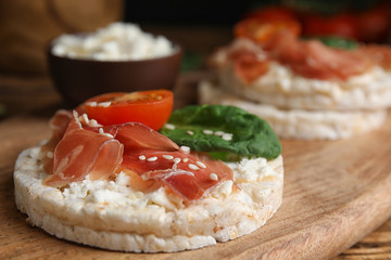 Puffed rice cake with prosciutto, tomato and basil on wooden board, closeup