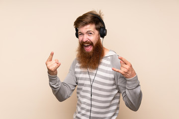 Redhead man with long beard over isolated background using the mobile with headphones and dancing