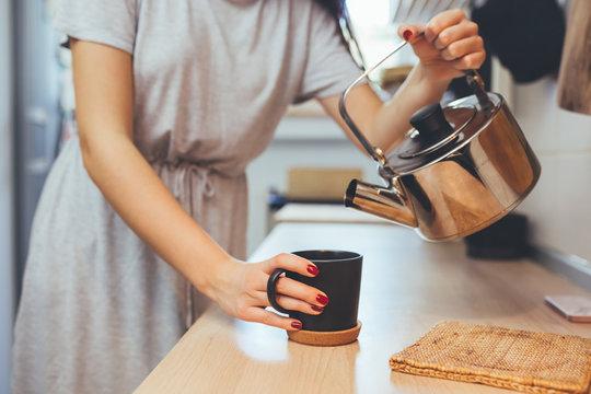 woman in kitchen drinking coffee or tea