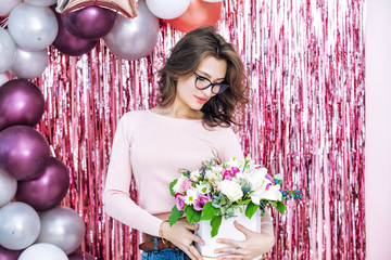 Young adult beautiful and happy woman model holding flowers portrait on festive background
