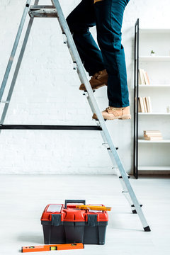 cropped view of worker climbing ladder near tool box