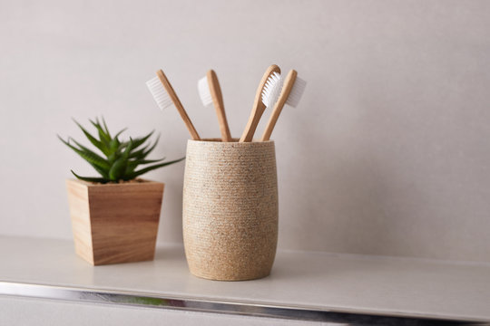 Ecological bamboo toothbrushes in bathroom with copy space