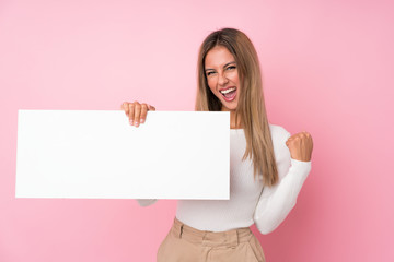 Young blonde woman over isolated pink background holding an empty white placard for insert a concept Fototapete