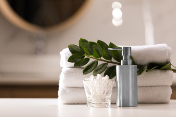 Obraz Composition with soap dispenser and towels on white table indoors - fototapety do salonu
