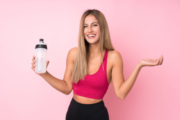 Young sport blonde woman over isolated pink background with sports water bottle