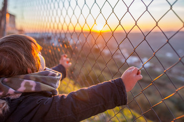 Kid boy holding hands on wire fence at sunset
