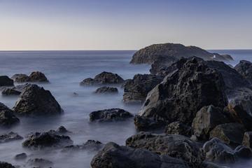 Volcanic rocks in Atlantic ocean, long exposure photography, horizon with sunset light, San Juan de la Rambla coastline, Tenerife, Canary islands, Spain