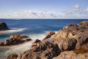 Volcanic rocks in Atlantic ocean, long exposure photography, horizon view with afternoon sunlight, Garachico, Tenerife, Canary islands, Spain