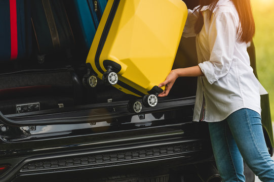 Asian woman lifting yellow suitcase into SUV car during travel in long weekend trip. People lifestyles and transportation concept. Girl put luggage from car trunk to vacation camping in summer time