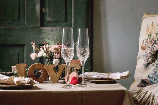 st. Valentines day or wedding romantic table setting with wooden letters love, needle felted hearts, ceramic plates, bouquet of pink roses, couple glasses of champagne on natural linen tablecloth.