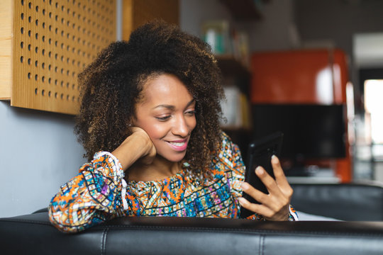 Casual young black woman relaxing at home using smartphone. Home leisure and tranquility concept. Afro hairstyle model.