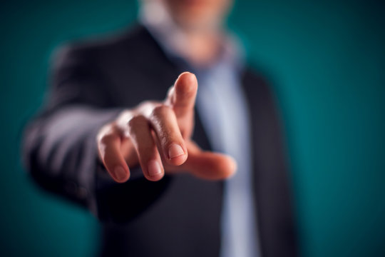 Businessman in suit pressing virtual button or pointing at something