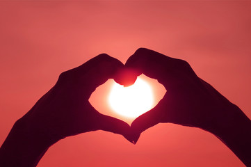Pop art style silhouette of woman's hand posing LOVE HEART sign against bright sun in red