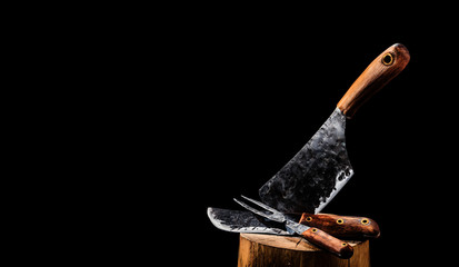Rustic butcher meat knife, cleaver and fork on black background