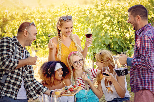 Young friends enjoying time together outside in vineyard - Youth friendship and wine tours concept