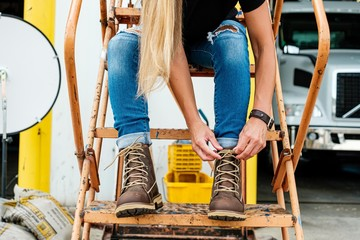 Woman tying shoe laces of boots