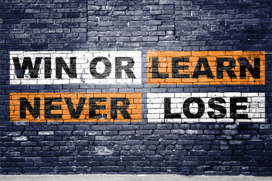 Win or learn never lose saying lettering Graffiti on Brick Wall