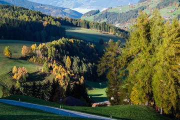 Autumn Santa Magdalena famous Italy Dolomites mountain village environs grassy hills and secondary road. Picturesque traveling, seasonal and countryside beauty concept background.