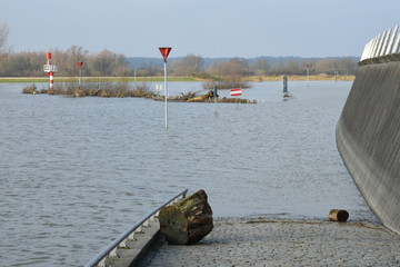 washed up rubbish on the banks and quays of flooded river IJssel in Doesburg