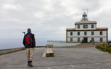 A pilgrim is at his longing goal. He is at the end of the world in Galicia. The hiker has reached the end of the Way of St. James, the lighthouse of Finisterre.