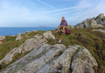 A hiker is resting. He sits on a rock in northern Spain in Galicia on the Atlantic coast and looks at the sea. It is afternoon. A very beautiful rocky coast.