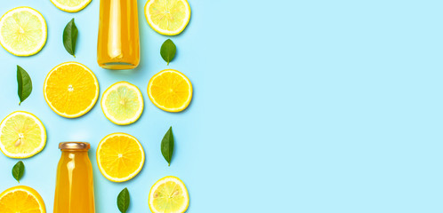 Flat lay composition with glass bottles of juice or fresh, slices of fresh lemon and orange, green leaves, ice cubes on blue background top view copy space. Citrus Juice Concept, Vitamin C, Fruits