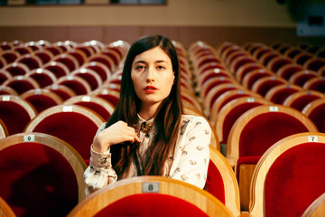 portrait of a pretty girl hipster in a movie theater posing in fashion style, dreaming alone
