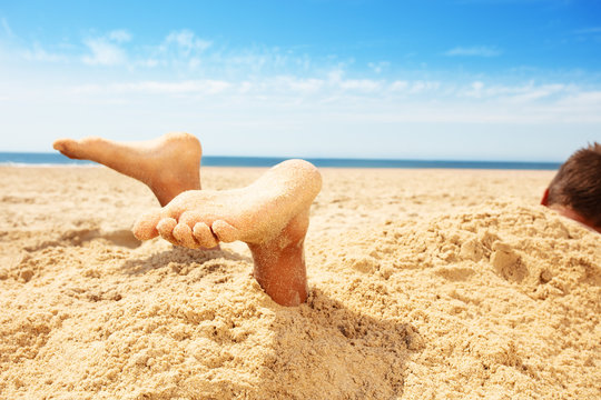 Legs and feet boy covered by sand in a game on sea