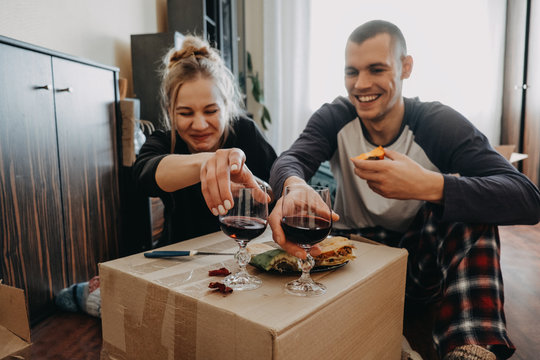 Moving Day, new home, Valentine's Day, unpacking boxes, newlyweds concept. Couple Celebrating Moving Into New Home With wine
